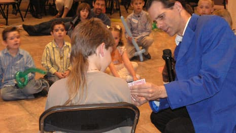 An adult volunteer helps a magician perform a funny-looking mini illusion!