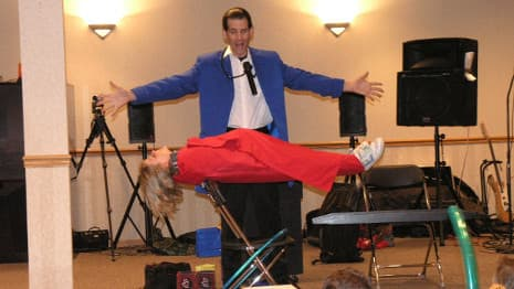 The magician performs an illusion in which a young volunteer levitates in mid-air!