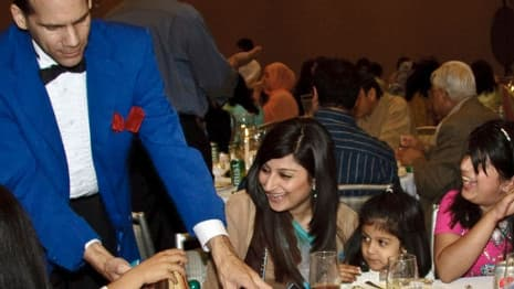 A magician entertains a group of women and children with a close-up magic trick at a Chicago event.
